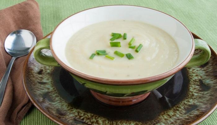Суп-пюре из картофеля с белокочанной капустой в чашке посыпанный зеленью