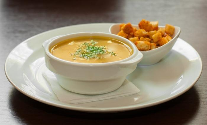 Суп-пюре из корнеплода с сухариками на тарелке