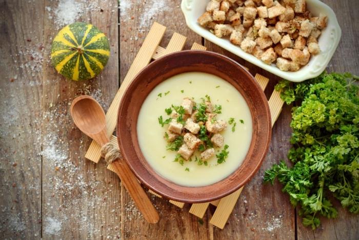 Суп-пюре из картофеля украшенный зеленью и сухарями