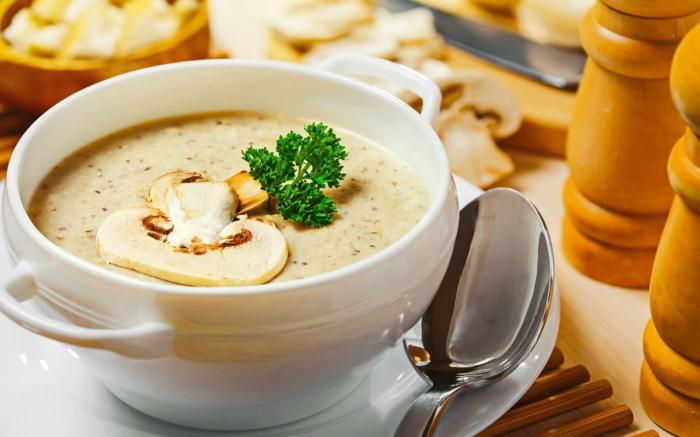 Суп-пюре из шампиньонов со сливками в чашке и украшенный зеленью