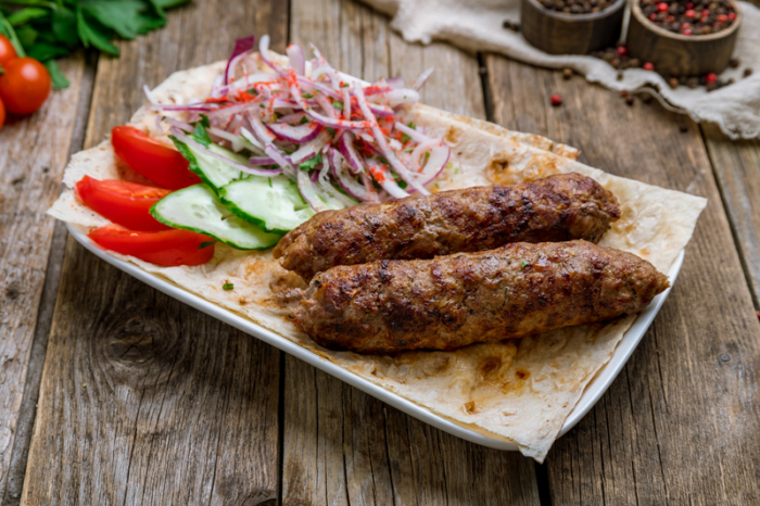 Люля кебаб из свинины с сезонными овощами на тарелке