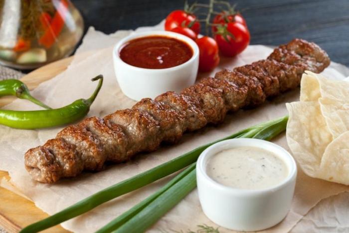 Люля кебаб из говядины на доске с овощами