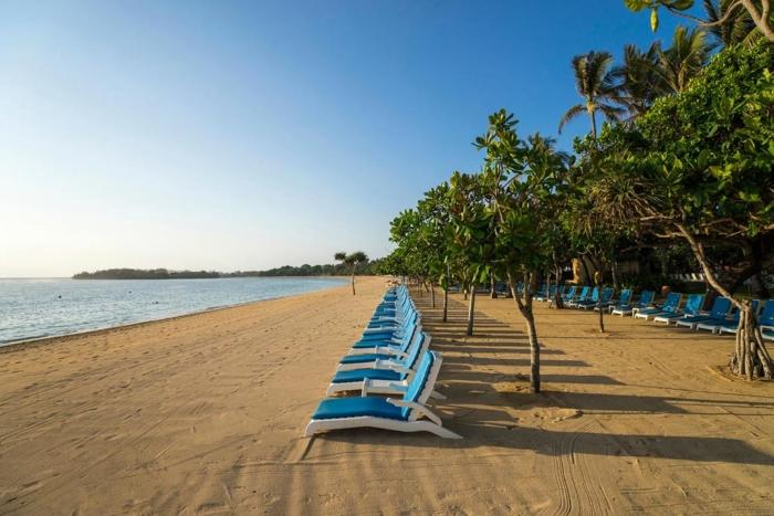 Голубые шезлонги вдоль пляжной линии Нуса Дуа