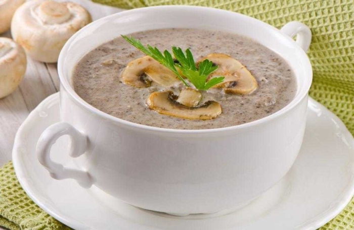 Суп пюре из шампиньонов и молока в белой чашке