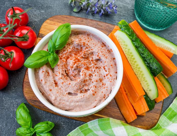 Хумус из красной фасоли в чашке поданный с огурцами и морковью