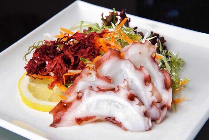 Ломтики сырого осьминога на тарелке с листьями салата