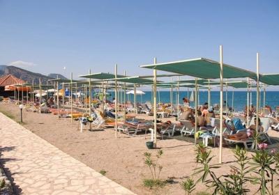 Пляж и шезлонги с отдыхающими