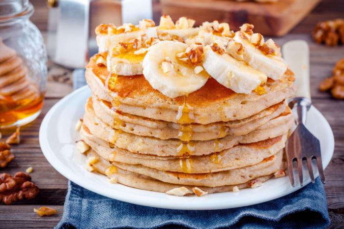 Банановые оладьи с орехами и сиропом на тарелке