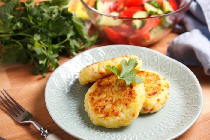 Золотистые котлеты с сыром и творогом на тарелке с зеленью