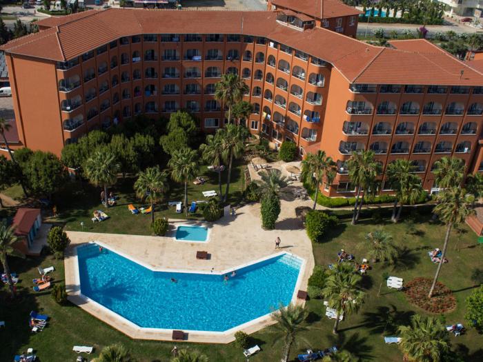Знаменитое здание отеля Turtas Club кирпичного цвета