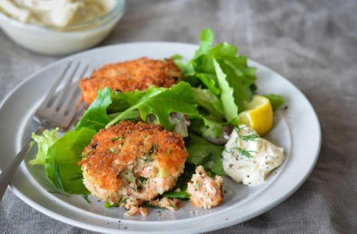 Белая тарелка с котлетами из семги и салатом с лимоном